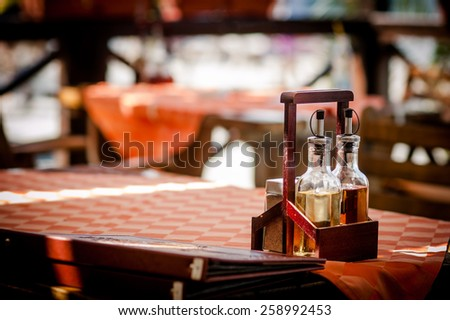 Restaurant tables in small europe sea town - stock photo
