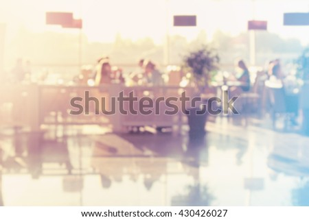Restaurant with many people eating. Pastel colors. Blurred image. - stock photo