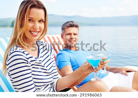 Restful female with cocktail sitting on deckchair and looking at camera with happy man on background - stock photo