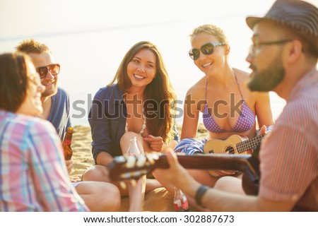 Restful friends spending vacations on sandy beach - stock photo