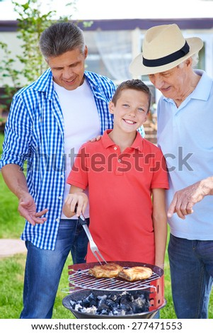 Restful senior man, young man and boy cooking meat on grill outdoors  - stock photo