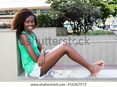 Resting african american woman in a green shirt - stock photo