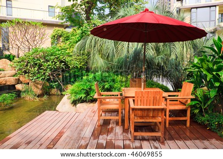 Resting area with tables and wooden chairs under umbrella in garden - stock photo