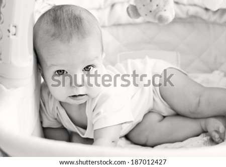 resting baby in the bed looking at the camera ( black and white ) - stock photo