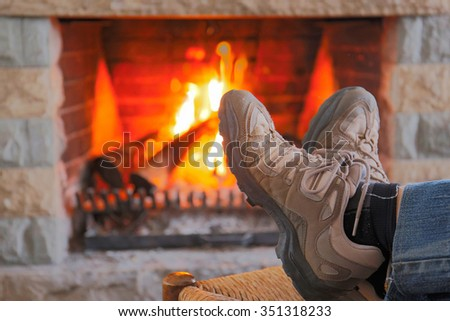 Resting Feet Beside the Fireplace - stock photo