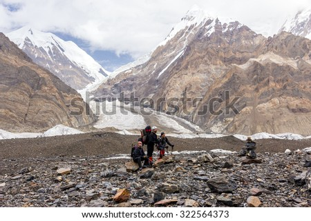 Resting Group of People in Mountains Group of Alpine Climbers Resting on Stone Surface of Glacier with High Peaks and Glacier Flow on Background - stock photo