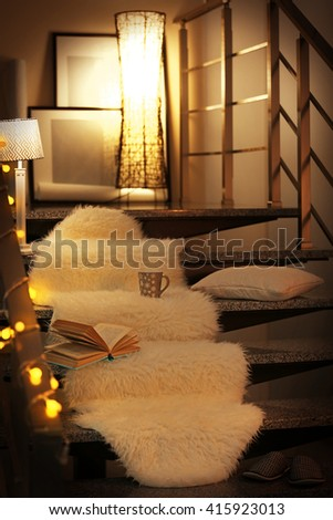 Resting-place with electric garland, cup of tea, book and lamps on modern stairs - stock photo