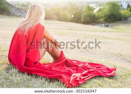 Resting superhero, blonde wonderwoman posing outdoor - stock photo