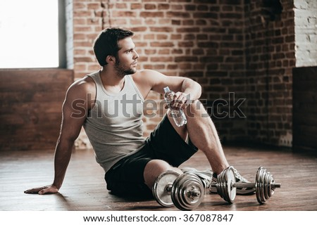 Resting time. Confident muscled young man wearing sport wear and sitting on the floor with bottle of water in loft interior  - stock photo