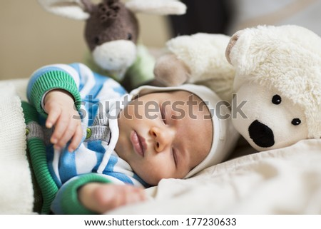 Resting time: Sweet peaceful baby boy sleeping during day time surrounded by toys. - stock photo