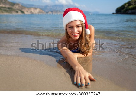 Resting woman in Santa's hat on a beach - stock photo