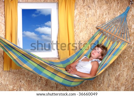 Resting young girl on a hammock in living room - stock photo