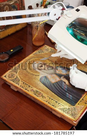 restoration of ancient gilded icon with  filling knife at workshop - stock photo