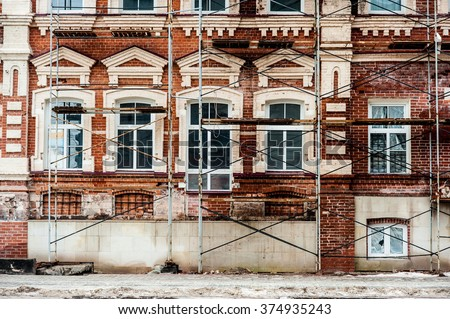 Restoration of old building  with white windows and red blocks - stock photo