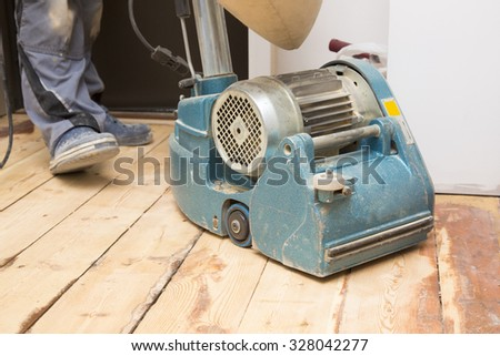 restore the old plank floor with grinding machine - stock photo
