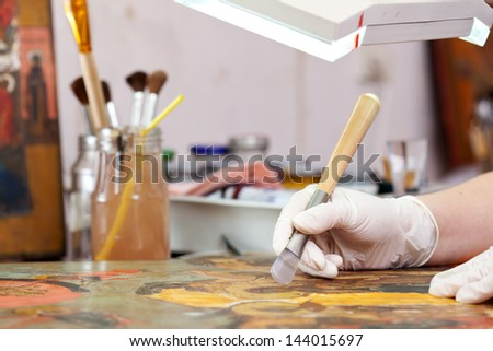 Restorer working on the ancient Christian icon with agate burnisher - stock photo