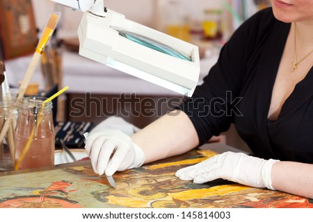 Restorer working on the ancient icon at restoration workshop - stock photo