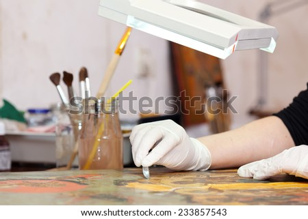 Restorer working on the old  icon at restoration workshop - stock photo