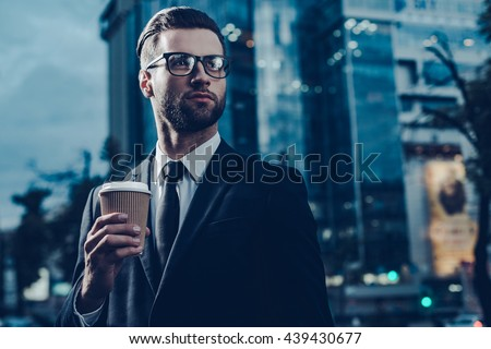 Restoring energy. Night time image of confident young man in full suit holding coffee cup and looking away while standing outdoors with cityscape in the background  - stock photo