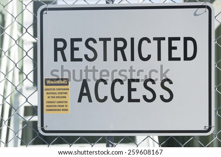 Restricted Access Sign at fence of property building, warning of asbestos material, health risk and hazard, blurred background. - stock photo