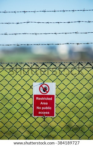 Restricted area sign on a chain linked and barbed wire fence - stock photo