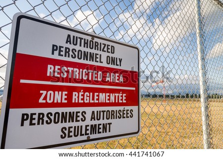 Restricted area sign on an airport fence with a windsock in the background. - stock photo
