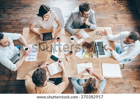 Results and teamwork. Top view of group of six people discussing something while sitting at the office table - stock photo