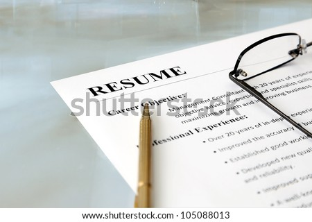 Resume on the Table. Closeup of resume with pen and glasses on the table - stock photo