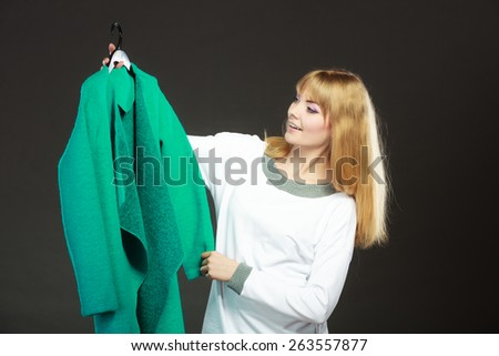 Retail and sale. Blonde girl fashionable woman buying clothes. Client customer holding hanger with green coat dark background - stock photo