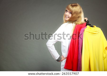Retail and sale. Blonde girl fashionable woman buying clothes. Client customer holding hangers with vivid color clothing gray background - stock photo