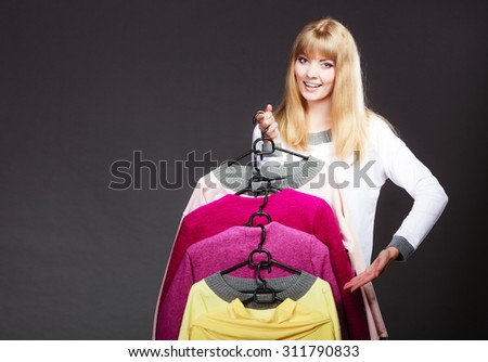 Retail and sale. Blonde girl fashionable woman showing clothes. Client customer holding hangers with clothing making inviting hand gesture - stock photo