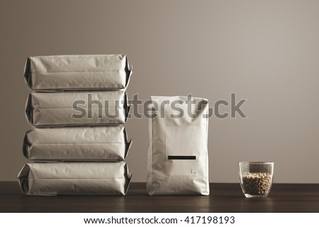 Retail pack: Big hermetic package with blank label presented near other four lying pouches filled with goods, near transparent glass with raw sampled coffee beans on red table, isolated - stock photo