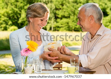 Retired Caucasian couple smiling and  holding gift outdoors - stock photo