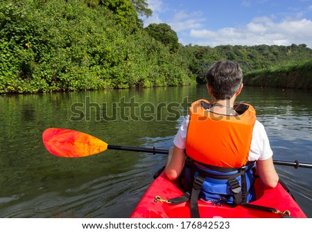 Retired caucasian lady in a red canoe or sea kayak on Hanalei river approaching the old steel bridge in Kauai - stock photo