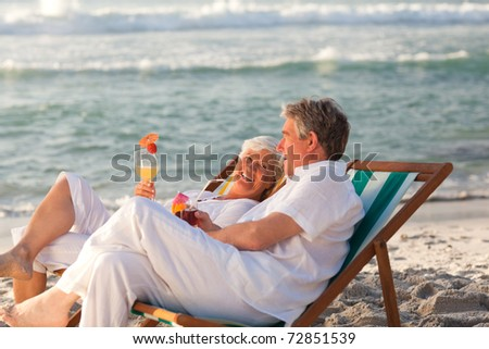 Retired couple drinking a cocktail - stock photo