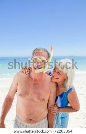 Retired couple on the beach - stock photo