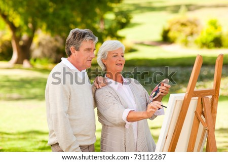 Retired couple painting in the park - stock photo