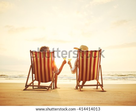 Retired couple watching the sunset enjoying a glass of wine - stock photo