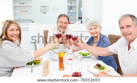 Retired friends toasting together at home - stock photo