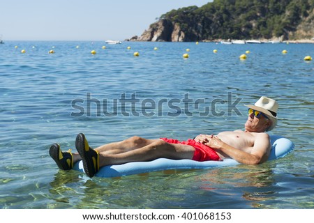 Retired man laying on inflatable bed floating in the sea - stock photo