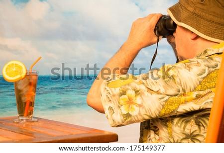 Retired man on exotic beach with binoculars watching ocean horizon  - stock photo