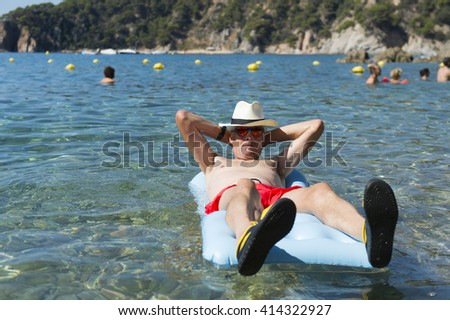 Retired man playing with inflatable bed floating in the sea - stock photo