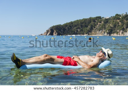 Retired man sleeping with inflatable bed floating in the sea - stock photo