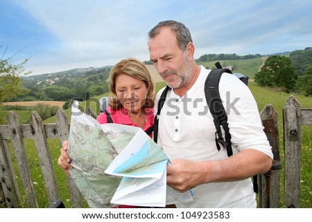 Retired people reading map on trekking day - stock photo