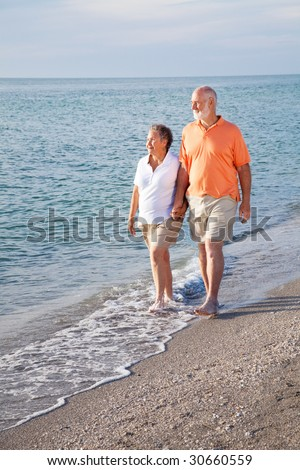Retired senior couple takes a romantic stroll on the beach. - stock photo