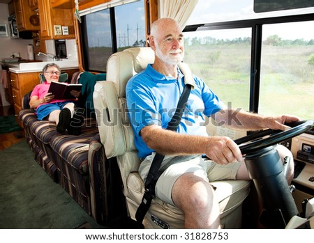 Retired senior couple traveling by motor home.  The husband drives while the wife reads in back. - stock photo