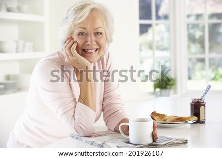 Retired woman eating breakfast - stock photo