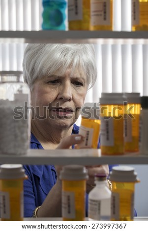 Retired woman looks over her medication - stock photo