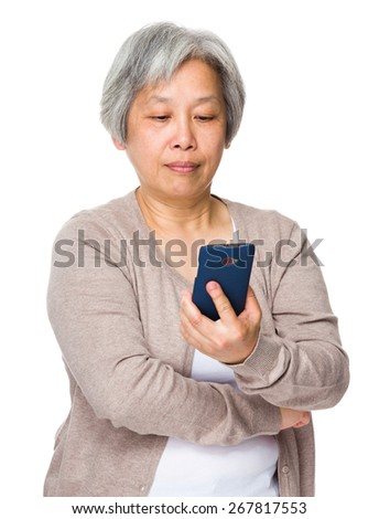Retired woman read on cellphone - stock photo