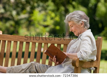 Retired woman reading a book on the  bench - stock photo